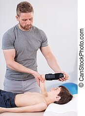 Physiotherapist training with boy