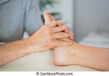 Physiotherapist treating patients foot in bright office