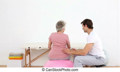 Physiotherapist watching patient stretch band -...