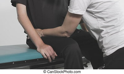 Closeup of physiotherapist exercising with disabled person on a therapy table.