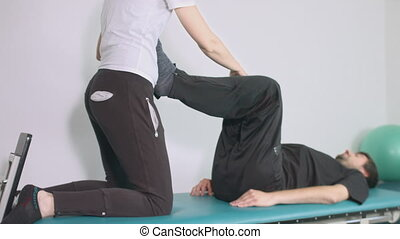 Physiotherapist exercising with disabled person on a therapy table.