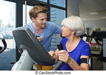 physiotherapist with senior woman using exercise machine