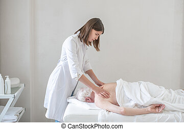 Physiotherapist working with a female patient in a rehabilitation center