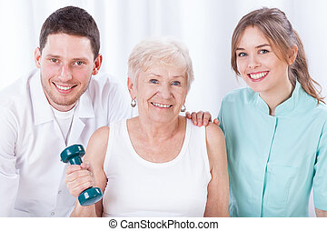 Physiotherapists and exercising elderly woman