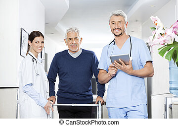 Physiotherapists And Senior Patient In Rehab Center