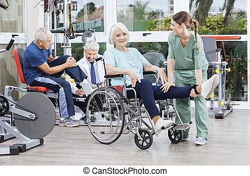Physiotherapists Guiding Senior Patients To Exercise At Rehab Ce