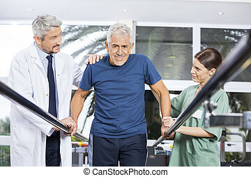 Physiotherapists Motivating Senior Man To Walk Between Parallel