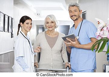physiotherapists, staand, met, vrouwlijk, patiënt, gebruik, walker