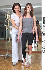 Physiotherapy at woman with hurt ankle
