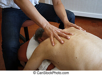 Physiotherapy - Phystiotherapist massaging back of senior ...