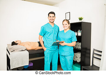 Physiotherapy Professionals With Clipboard Standing By Patient In Bed