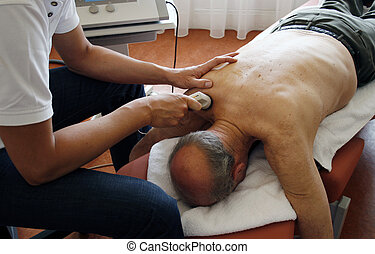 physiotherpist works with ultrasound on senior patient