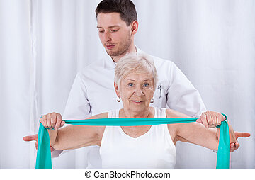 Physiotheraqpist assisting elderly woman in exercising