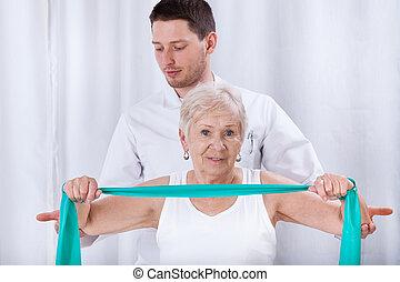 physiotheraqpist, pomagając, starsza kobieta, w, wykonując