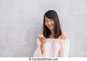 piękna kobieta, ściana, na, konkretny, asian, używając, cellphone