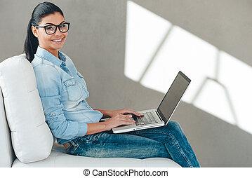 piękna kobieta, pracujący, posiedzenie, szary, laptop, blogger., młody, przeciw, leżanka, patrząc, znowu, aparat fotograficzny, tło, uśmiech, okulary, widok budynku