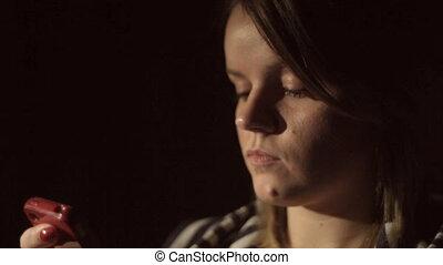 piękna kobieta, przeglądnięcie, smartphone, w, ciemny pokój
