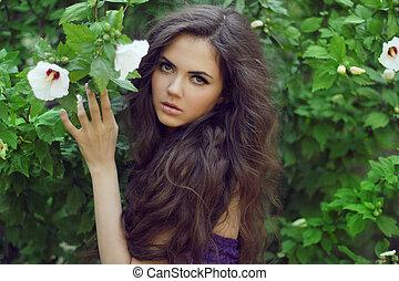 piękna kobieta, z, kędzierzawy, długi, hair., outdoors, portret, na, zielone tło, lato, nature.