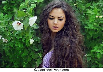 piękna kobieta, z, kędzierzawy, długi, hair., outdoors, portret, na, zielone tło, spoczynek, w parku