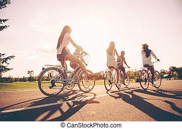 piękny, cieszący się, kąt, ludzie, razem., młode przeglądnięcie, bicycles, niski, jeżdżenie, wzdłuż, szczęśliwy, dzień, droga, prospekt