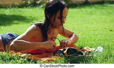 piękny, song., kobieta, sunglasses, ruchomy, młody, trawa, telefon, muzykować słuchanie, używa, śpiew, leżący