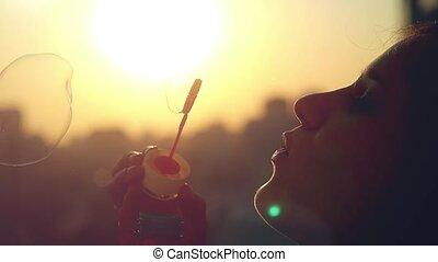 piękny, uśmiecha się, powolny, miasto, młody, ruch, kobieta, zachód słońca, podmuchowa bańka, szczęśliwy