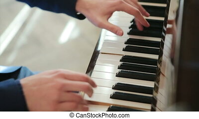pianist in blue suit plays rapidly on the piano. top view,...