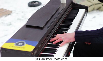 Pianist in the mask plays the piano on the street in the...