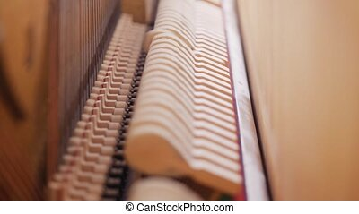Piano hammers hitting strings inside an old piano. Slow...