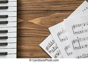 piano keyboard on wooden background with notes