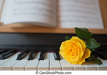 Piano keyboard with music book and yellow rose