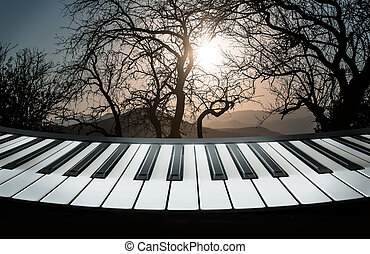 Piano keys against the backdrop of a mountain landscape with trees