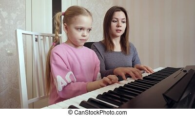 Young woman teaches little girl to play the piano. - Piano...