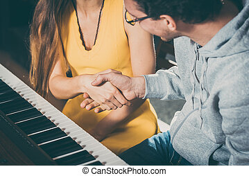 Piano teacher and student shaking hands after lesson