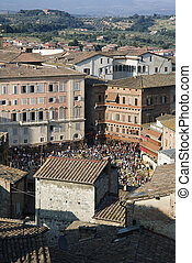 Rooftop view of Piazza del Campo with crowd gathered.