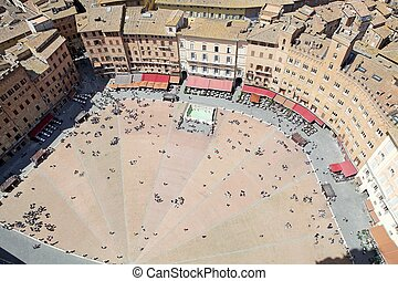 Piazza del Campo view from Torre del Mangia. Piazza del Campo is the principal public space of the historic centre of Siena, Tuscany, Italy. The mansions that line the shell-shaped square have unified the rooflines. The twice a year horse race, Palio di Siena, is held around the edges of the square...