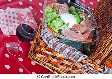 Pic-nic basket with salad and glass of wine