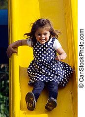 piccola ragazza, diapositive, in, campo di gioco