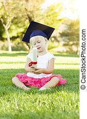 piccola ragazza, in, erba, il portare, berretto laurea, presa a terra, diploma, con, nastro