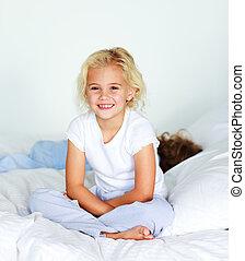 piccola ragazza, sedendo letto, sorridente, a, il, macchina fotografica