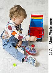 piccolo ragazzo, giochi, con, uno, automobile, e, trottola, giocattolo