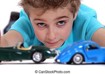 piccolo ragazzo, gioco, con, automobili giocattolo