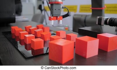 Pick and place robotic arm manipulator moving red toy blocks at robot exhibition