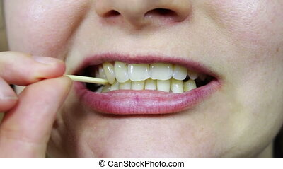 pick food from teeth with toothpick - girl picking with ...