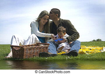 pick nick day - family outdoor in a field near water having...