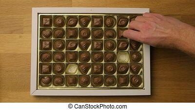 Box of chocolate bonbon candies put on a table and hands taking pieces