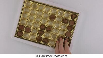 Box of chocolate bonbon, people fighting over it, grabbing a lot, tearing the box apart arguing