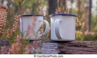 picking season and leisure concept - two cups of tea on log in forest