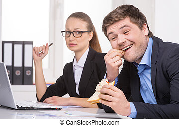 Picking teeth. Businessman picking teeth while sitting near his coworker