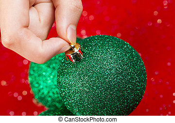 Picking up Green Christmas Ornament